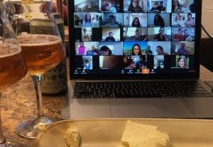 A laptop showing people on a zoom call with beer and cheese