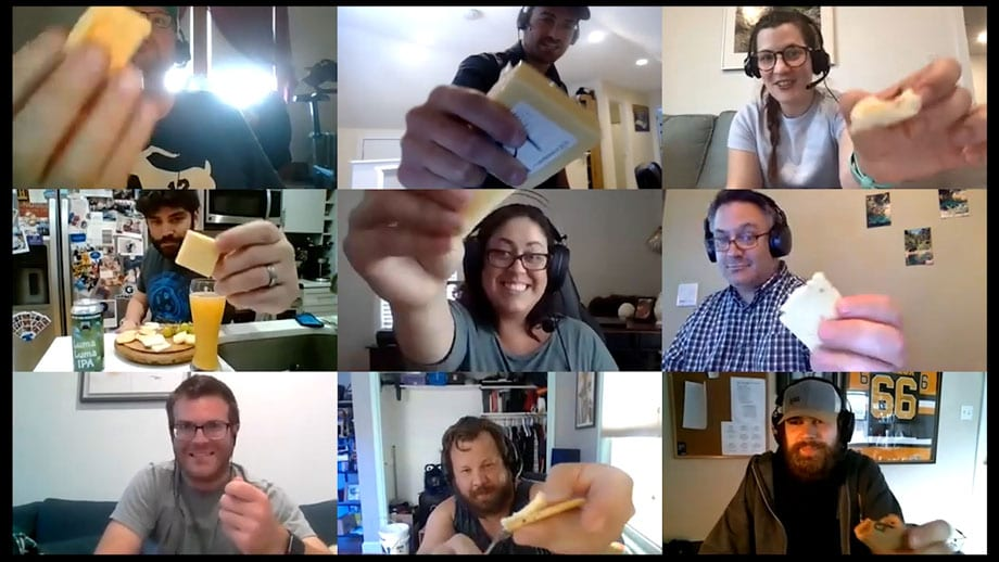 group shown via videoconference holding slices of cheese
