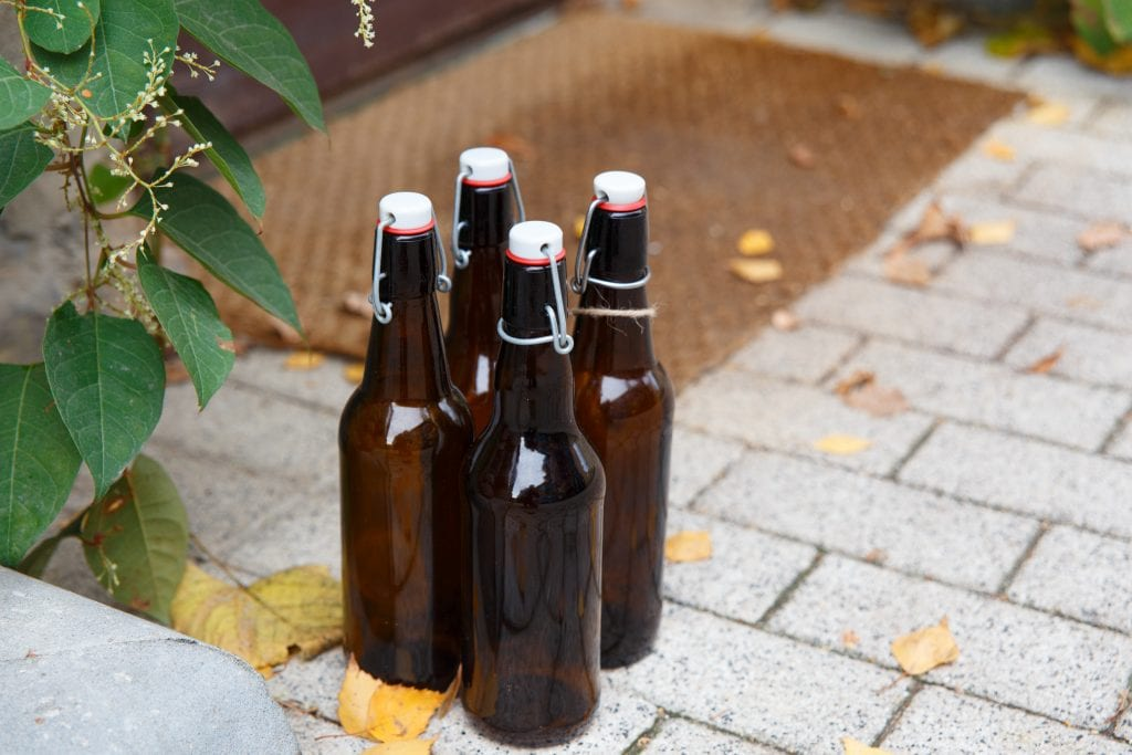 Four empty beer bottles on porch of house